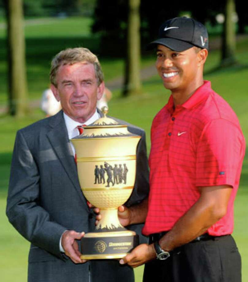 Tiger Woods had plenty to smile about in August when PGA Tour commissioner Tim Finchem presented him with the trophy for winning the Bridgestone Invitational tournament.