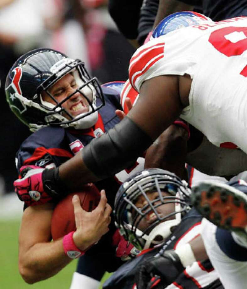 Texans quarterback Matt Schaub (left) is sacked by Giants lineman Rocky Bernard (top right) on Sunday in Houston.