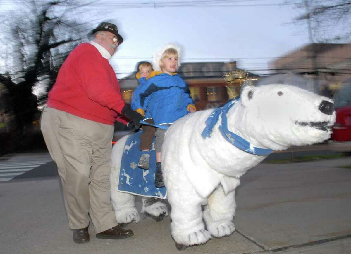 Bobby Jones, 4, front, and his brother, Mason, 3, of Greenwich, ride the mechanical polar bear with the help of Bob Meyer during the annual tree-lighting ceremony at Greenwich Town Hall, Friday afternoon, Dec. 3, 2010.
