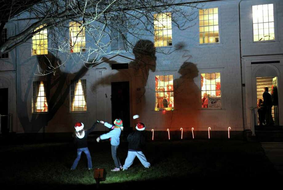 Highlights from the annual Tree Lighting Ceremony which was held at Town Hall Green in Fairfield, Conn. on Friday December 3, 2010. Making shadows on the side of the old academy building is Aidan Gombos, 9, at left, Lily Williams, 10, in center, and Aven Williams, 8. They are all from Fairfield. Photo: Christian Abraham / Connecticut Post