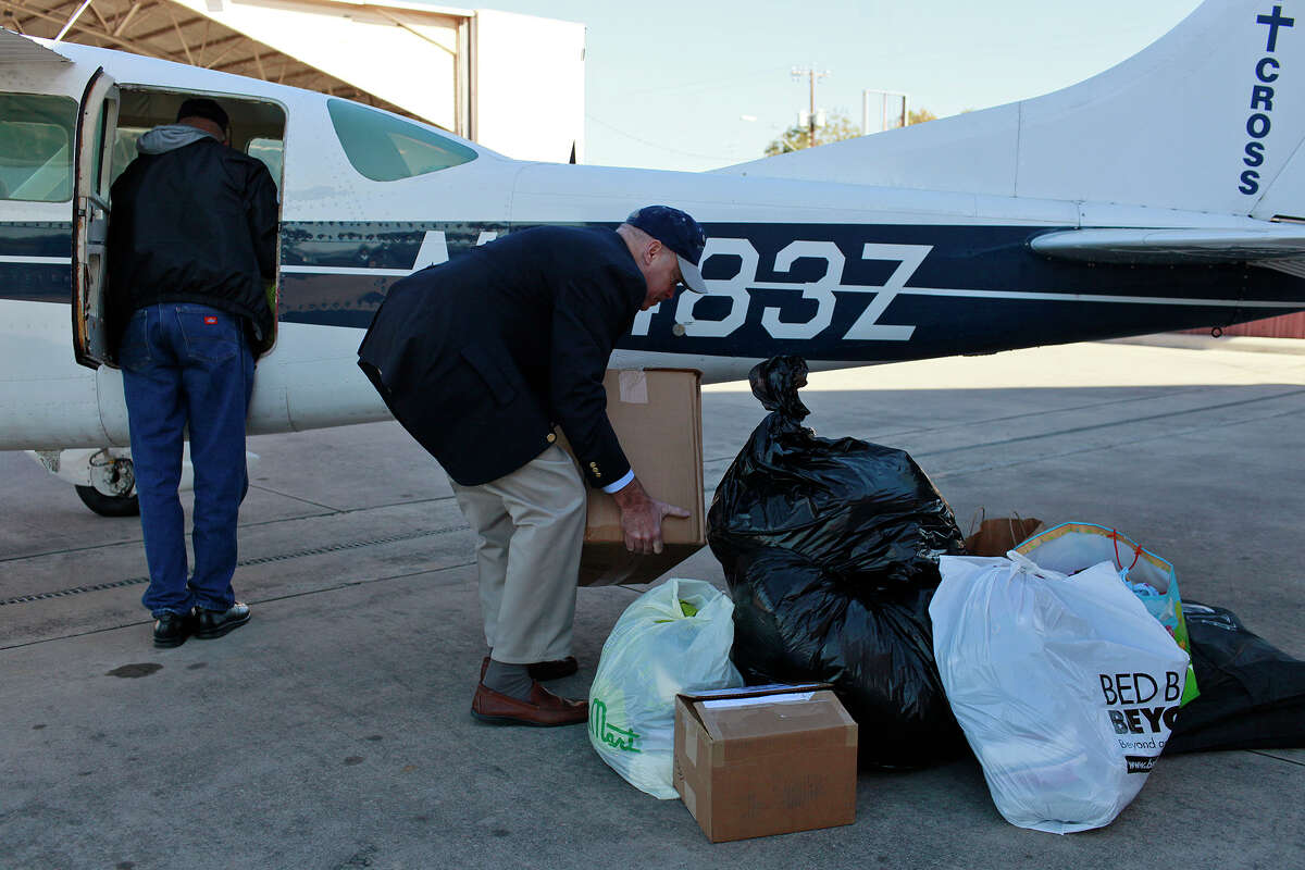 Sky Cross co-founder Terry Bliquez (left), with the help of David Young, the Sky Cross board vice president, prepares to fly supplies to the Texas-Mexico border from Stinson Municipal Airport.