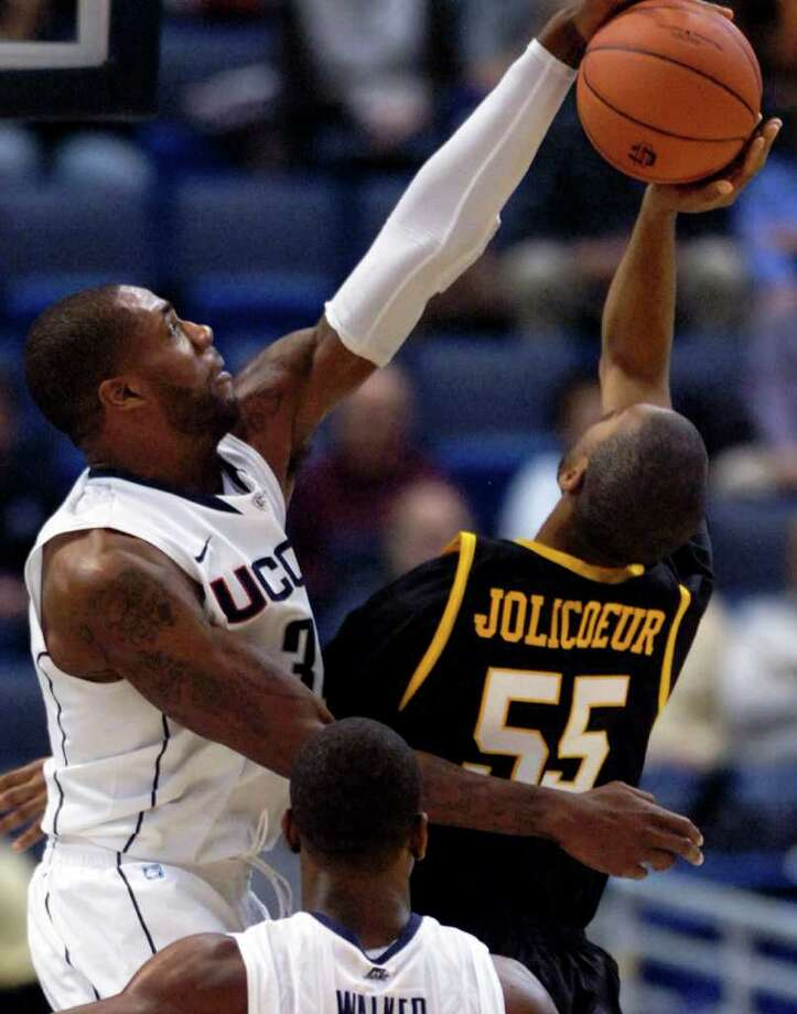 Connecticut's Alex Oriakhi, left, blocks the shot of UMBC's Laurence Jolicoeur during the first half of their NCAA college basketball game in Hartford, Conn., Friday, Dec. 3, 2010. (AP Photo/Fred Beckham) Photo: Fred Beckham, AP / FR153656 AP
