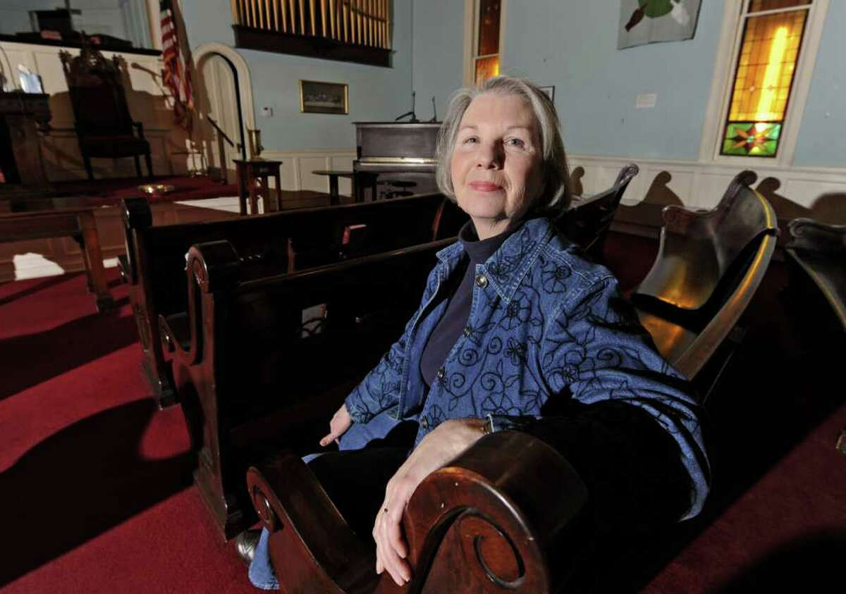 Linda O'Malley sits in a pew in the Oakwood Avenue Presbyterian Church in Troy, NY on December 2, 2010. The church has closed and Linda is working on turning the space into a community center. (Lori Van Buren / Times Union)