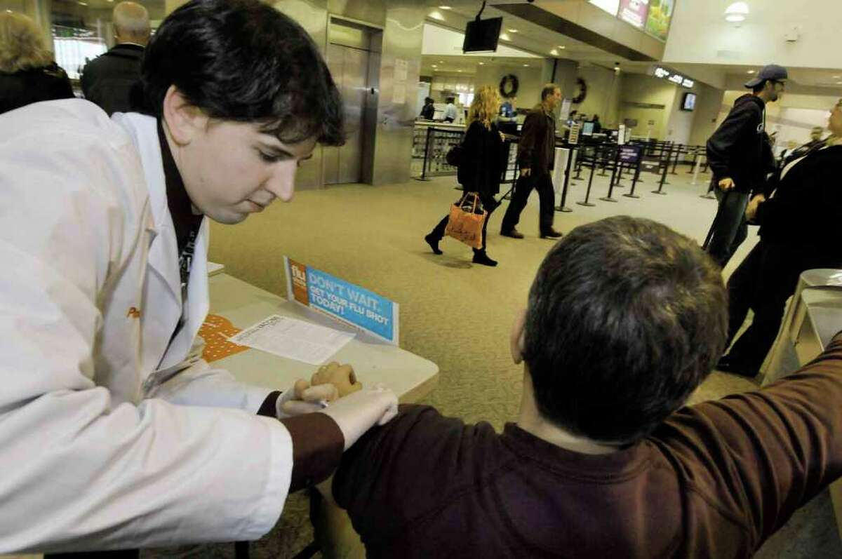 CVS pharmacist Brian Matthews,left, administers a flu shot to traveler Greg Moore of Brunswick at the Albany International Airport in Colonie 12/03/2010. ( Michael P. Farrell/Times Union )