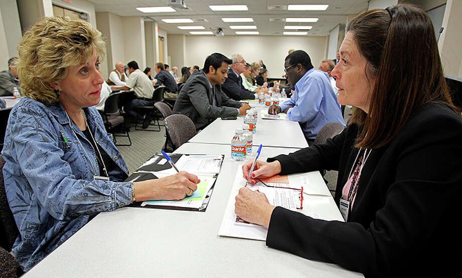 Sara Gill (left) with Family and Community Health Systems talks with Jannine Cody from Pediatrics/Genetics as the Institute for Integration of Medicine and Science and the Cancer Therapy and Research Center host a speed networking event at the UT Health Science Center on Dec. 3 at the municipal offices in Kenedy. Photo: Tom Reel /  2010 San Antonio Express-News
