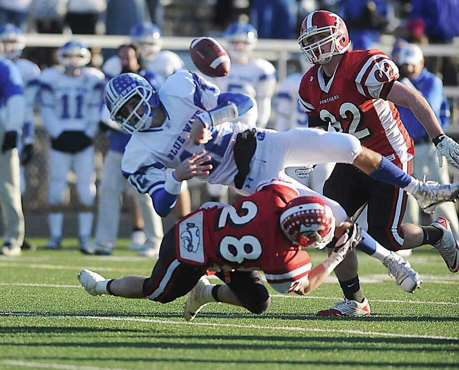 Masuk High School's Dean Accomondo forces a fumble on Darien High School's Chris Allam in the Class L semi-final fooball game at Shelton high School in Shelton, Conn., on Saturday December 4,  2010. Photo: Kathleen O'Rourke / Stamford Advocate