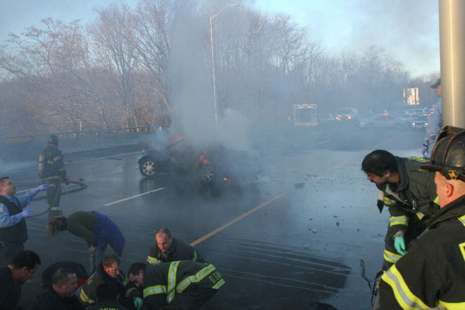 Fairfield firefighters battle a car fire on Interstate 95 Saturday afternoon that shut down southbound lanes of the highway between Exits 23 and 24. Photo: Contributed Photo/Fairfield Fire Department / Fairfield Citizen contributed
