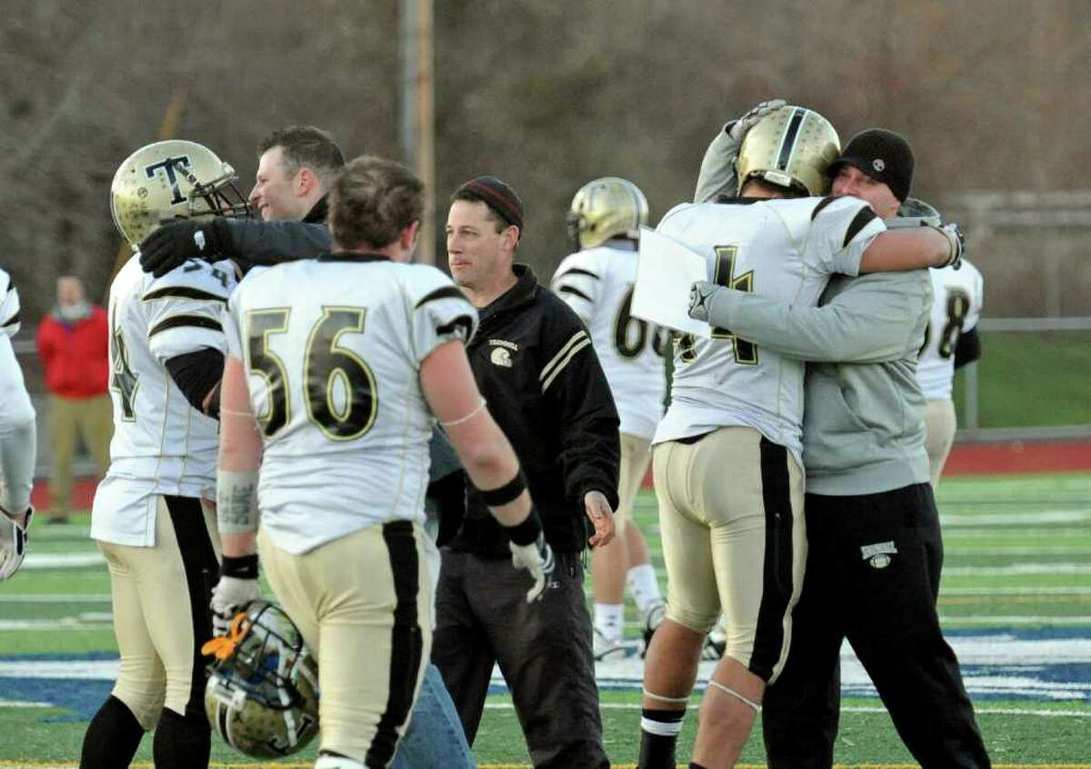 Trumbull coaches hug the players after defeating Norwich Free Academy, during Class LL semifinal football action in West Haven, Conn. on Saturday December 4, 2010. Trumbull beat Norwich 21-6.