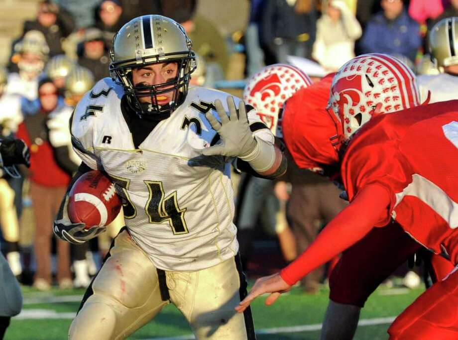 Trumbull's #34 Matt Lena looks to fend off a Norwich player, during Class LL semifinal football action against Norwich Free Academy in West Haven, Conn. on Saturday December 4, 2010. Trumbull beat Norwich 21-6. Photo: Christian Abraham / Connecticut Post