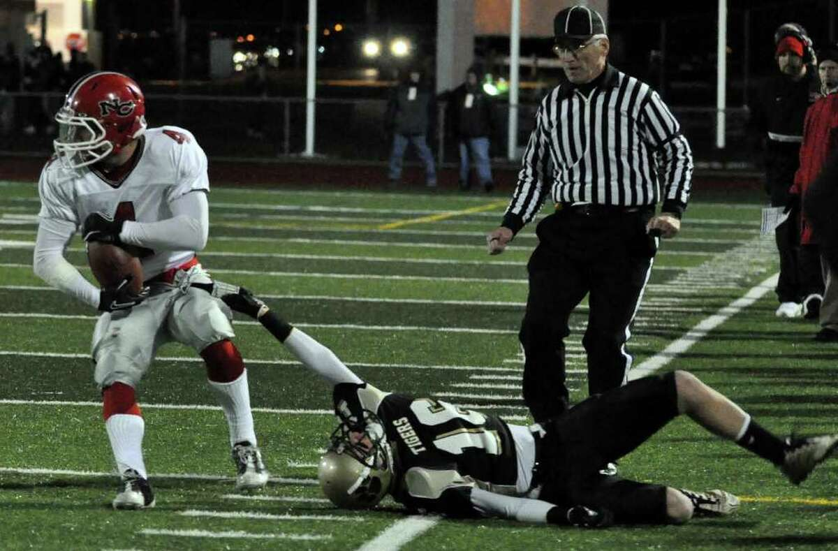 New Canaan's Kevin Macari (4) drags Daniel Hand's Vance Giarratana (16) for yardage during the CIAC Class L semifinals at Ken Strong Stadium in West Haven on Saturday, Dec. 4, 2010.