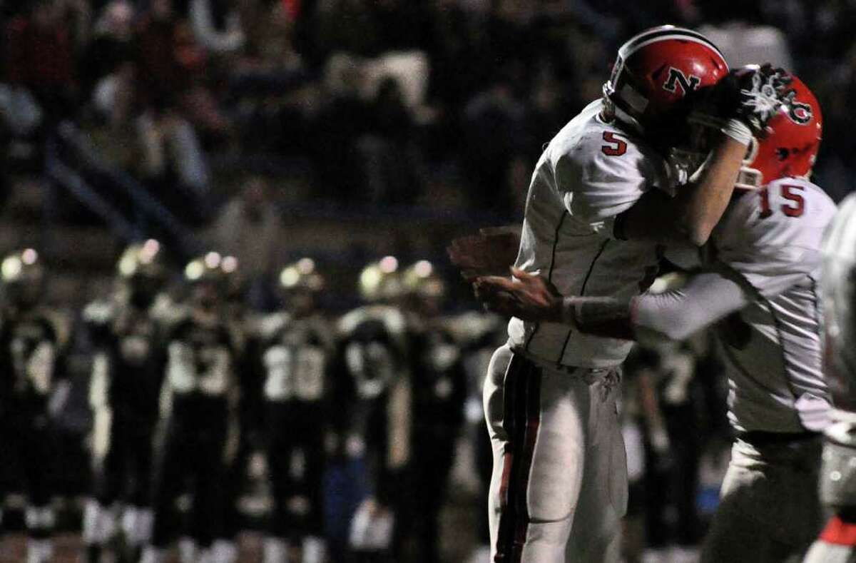 New Canaan's Joseph Costigan (5) and teammate Matthew Milano (15) celebrate a touchdown as Daniel Hand looks on from the sidelines during the third quarter of the CIAC Class L semifinals against Daniel Hand at Ken Strong Stadium in West Haven on Saturday, Dec. 4, 2010.