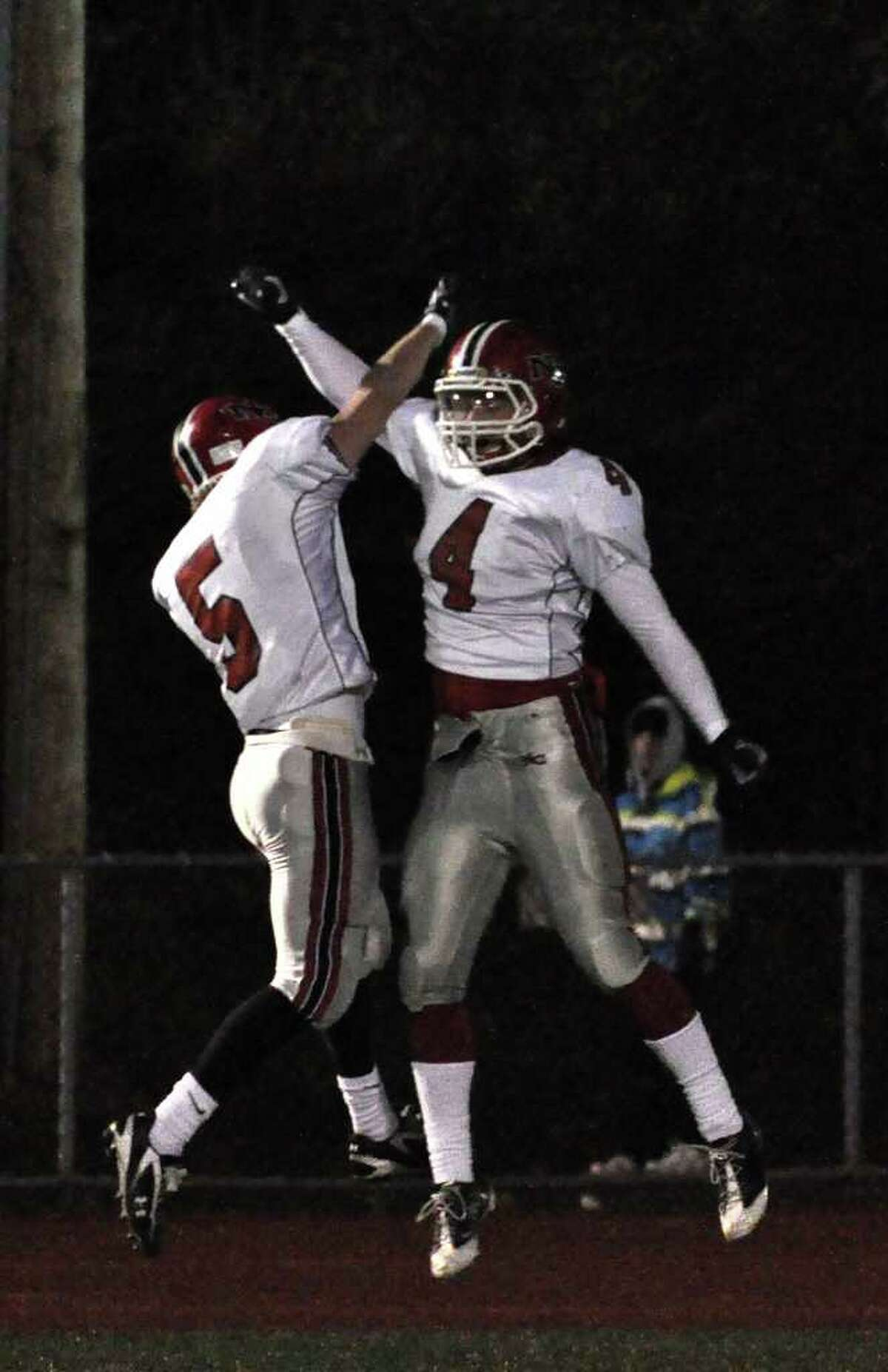 New Canaan's Joseph Costigan (5) and teammate Kevin Macari (4) celebrate a touchdown during the CIAC Class L semifinals against Daniel Hand at Ken Strong Stadium in West Haven on Saturday, Dec. 4, 2010.