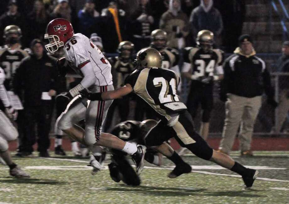 New Canaan's Cameron Armstrong (36) tries to avoid a tackle by Daniel Hand's Nicolas Vitale (21) during the CIAC Class L semifinals at Ken Strong Stadium in West Haven on Saturday, Dec. 4, 2010. Photo: Amy Mortensen / Connecticut Post Freelance