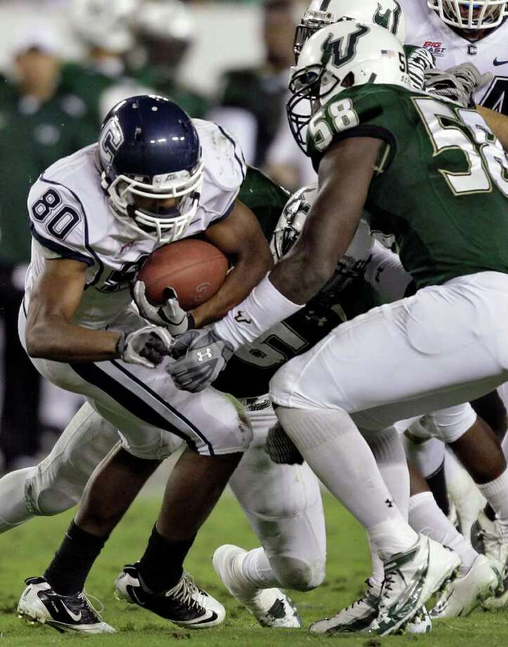 Connecticut wide receiver Michael Smith (80) is pulled down by South Florida linebacker Sam Barrington (36) and defensive end David Bedford (58) after a second-quarter reception during an NCAA college football game Saturday, Dec. 4, 2010, in Tampa, Fla. (AP Photo/Chris O'Meara) Photo: AP