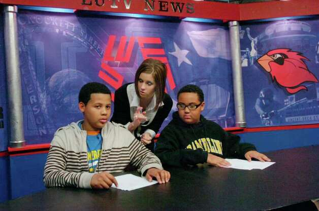 """Fox 4 news anchor/reporter, Jessica Guidry, center, works with  Romelle Boykins, left, and Jonathan Johnson, right, during a television news production workshop at Lamar University studios.  Some 250 seventh and eighth graders chosen from area schools participated Saturday in Kids College, a project of the P-16 Council of Southeast Texas, which works to help young people prepare to work and live in the """"outside world.""""  Saturday, December 4, 2010.  Valentino Mauricio/The Enterprise Photo: Valentino Mauricio / Beaumont"""