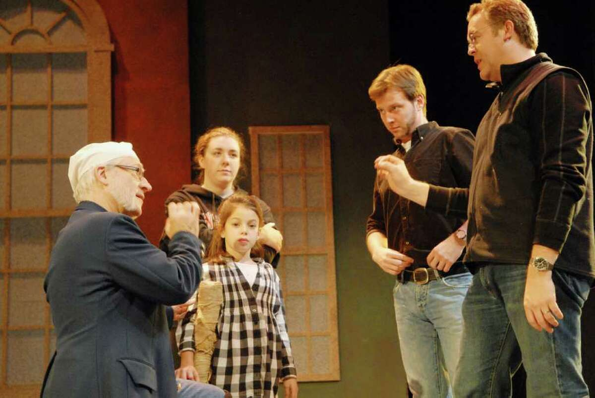 At left, actor Ron Komora, of Nassau, who stars as Ebenezer Scrooge, Kaitlin Stewart, of Troy, a NYSTI Intern, in the roll of Mrs. Cratchit, Sophie Mele, of Loudonville, as Tiny Tim, and Timothy Hull, of Waterford, who has the roll of Bob Cratchit, on stage with show director, Dave Baecker, during rehearsal of