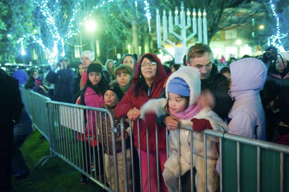 Spectators brave the cold as Heights & Lights returns to Stamford Downtown as Santa and his friends rappel down the Landmark Building before lighting the tree in Latham Park in Stamford, Conn., Sunday, December 5, 2010. Yankees General Manager Brian Cashman served as a repelling elf at this year's event.
