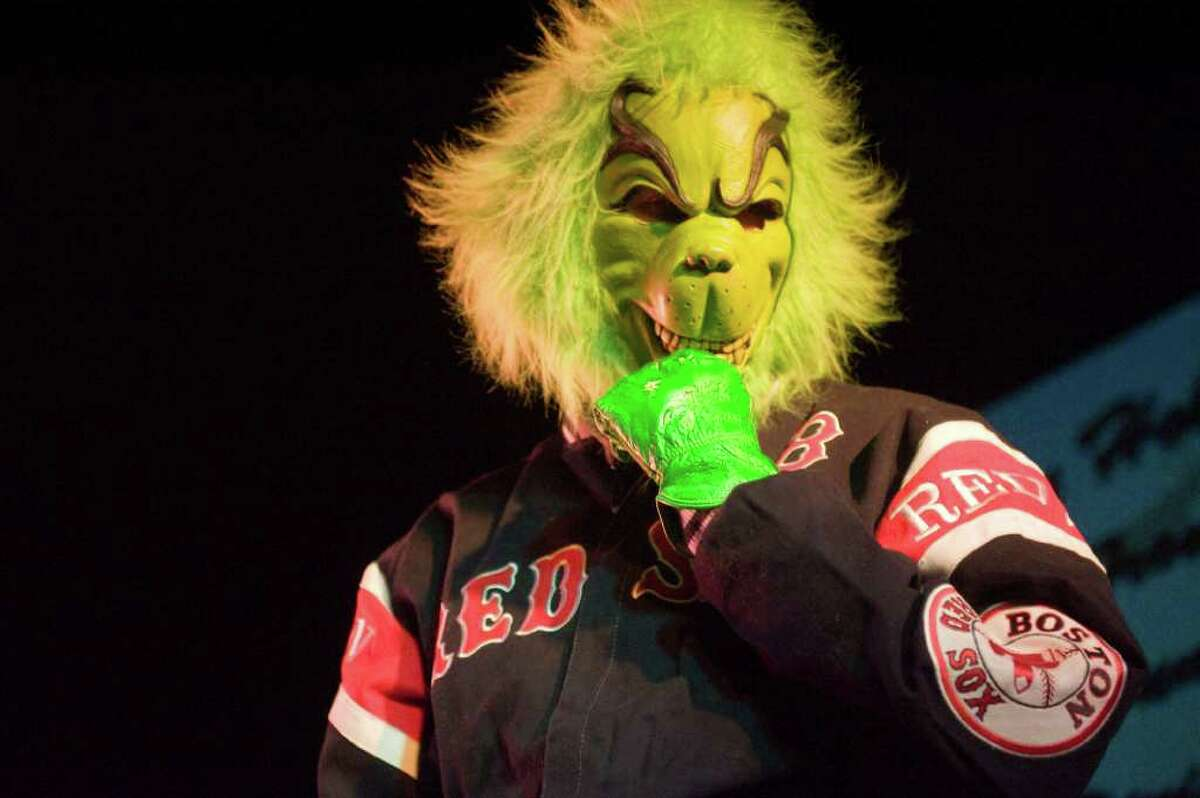 The Grinch shows his support for the Boston Red Sox despite, or because of the Heights and Lights special guest Yankees General Manager Brian Cashman in Stamford Downtown, Sunday, December 5, 2010. Cashman served as a repelling elf at this year's event. Following the repelling, the crowd moved up Bedford Street to Latham Park to light the tree for the season.