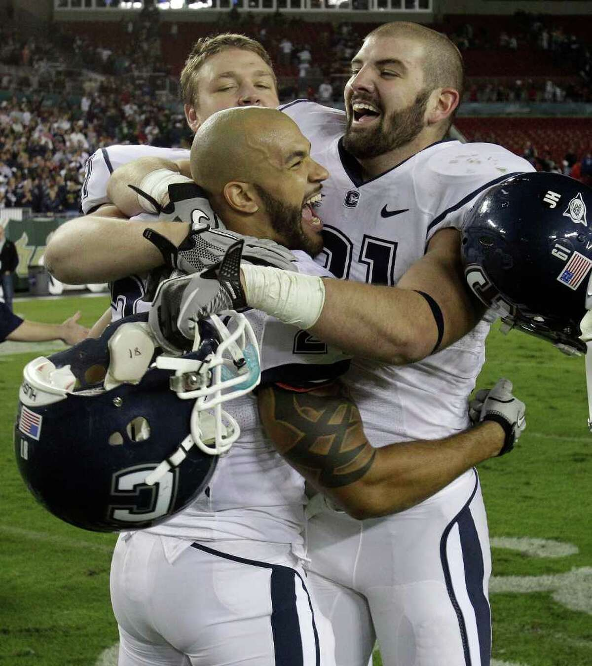 Connecticut running back D.J. Shoemate (24) celebrates with teammates Stephen Brown (61) and Jesse Joseph (91) after defeating South Florida 19-16 to clinch the Big East Conference title during an NCAA college football game Saturday, Dec. 4, 2010, in Tampa, Fla. (AP Photo/Chris O'Meara)