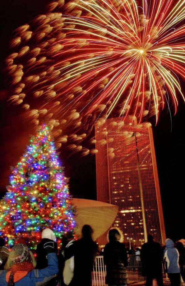 Just as the New York State Tree lights up with more than 2,000 energy-efficient light-emitting diodes, the crowd at Empire State Plaza was treated to a fireworks display to honor the holiday tree-lighting on Sunday, Dec. 5, 2010, in Albany, NY.    (Luanne M. Ferris / Times Union ) Photo: Luanne M. Ferris