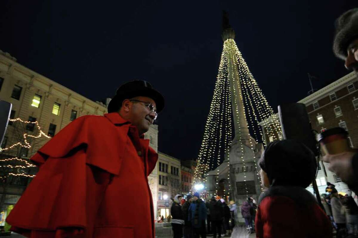 Troy Mayor Harry Tutunjian stands near the holiday tree after it was lit at Monument Square at the end of the 28th annual Victorian Stroll in Troy, NY on Sunday December 5, 2010. ( Philip Kamrass / Times Union )