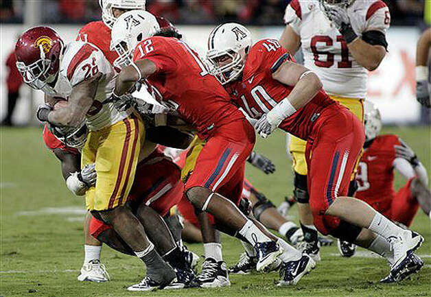 USC's Marc Tyler (26) is gang tackled by Arizona's Adam Hall (12), Derek Earls (40) and D'Aundre Reed (83, in back) on Nov. 13, 2010.