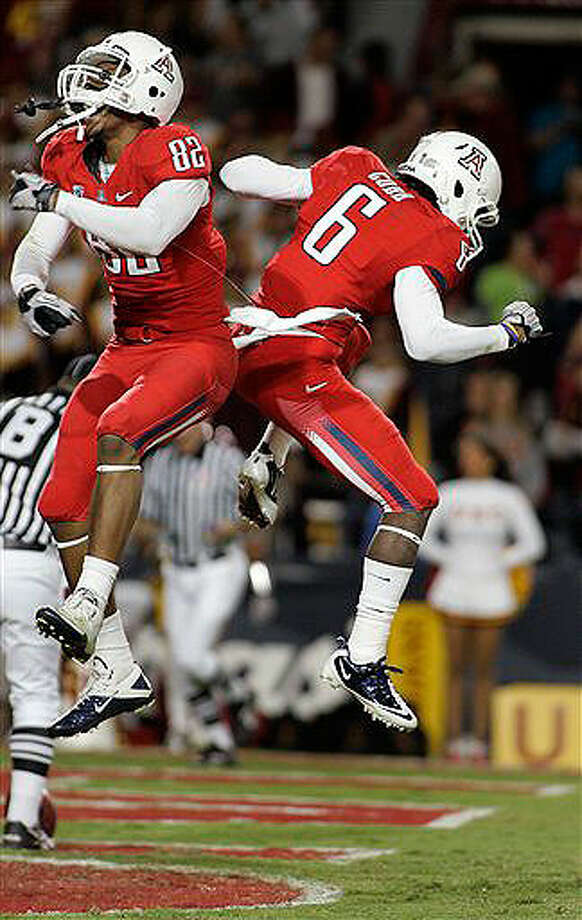 Arizona's Juron Criner (82) and Travis Cobb (6) celebrate Cobb's second-quarter touchdown catch against USC Nov. 13, 2010.