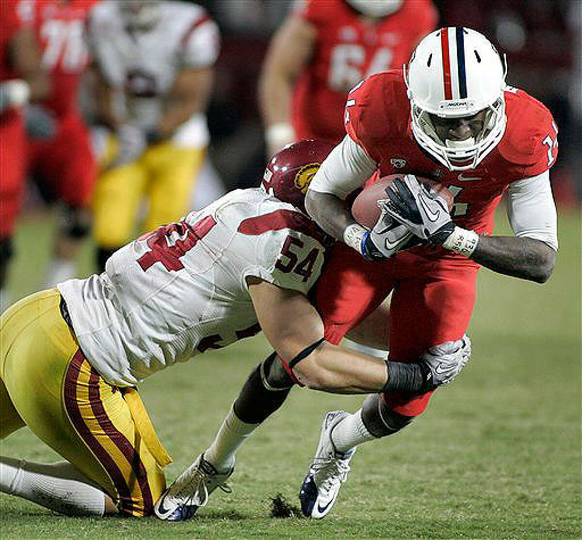 Arizona's Richard Morrison (14) is dragged down by USC's Chris Galippo (54) after a short gain on Nov. 13, 2010.