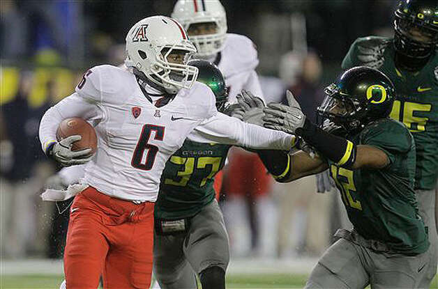 Arizona wide receiver Travis Cobb (6) stiff arms Oregon cornerback Brian Jackson (12) on Nov. 26, 2010.