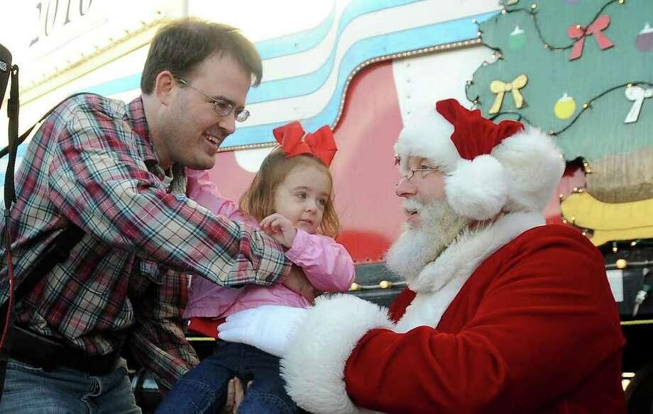 Before boarding the KCS Holiday Express, Mark Reynolds hands Chloe Reynolds to Santa. Guiseppe Barranco/The Enterprise Photo: Guiseppe Barranco / Beaumont