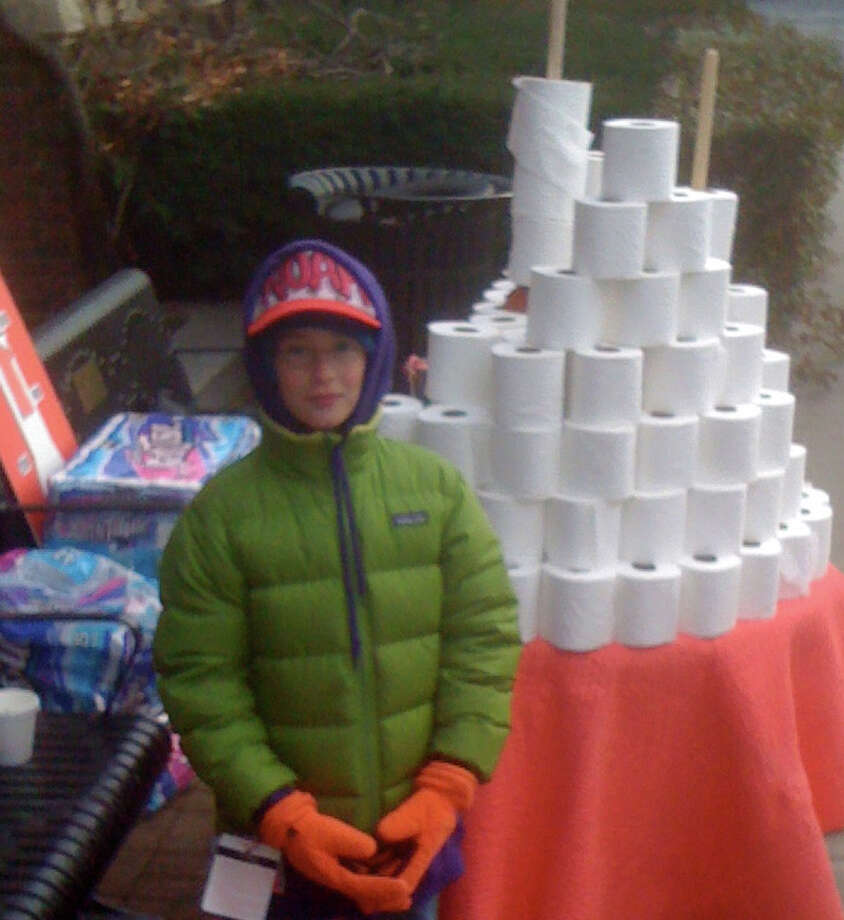 Noah Pines, braving frigid temperatures Sunday, stands next to a tower of toilet paper he was selling on Main Street in Westport to raise money to build a bathroom in a Habitat for Humanity house. Photo: Contributed Photo / Westport News contributed