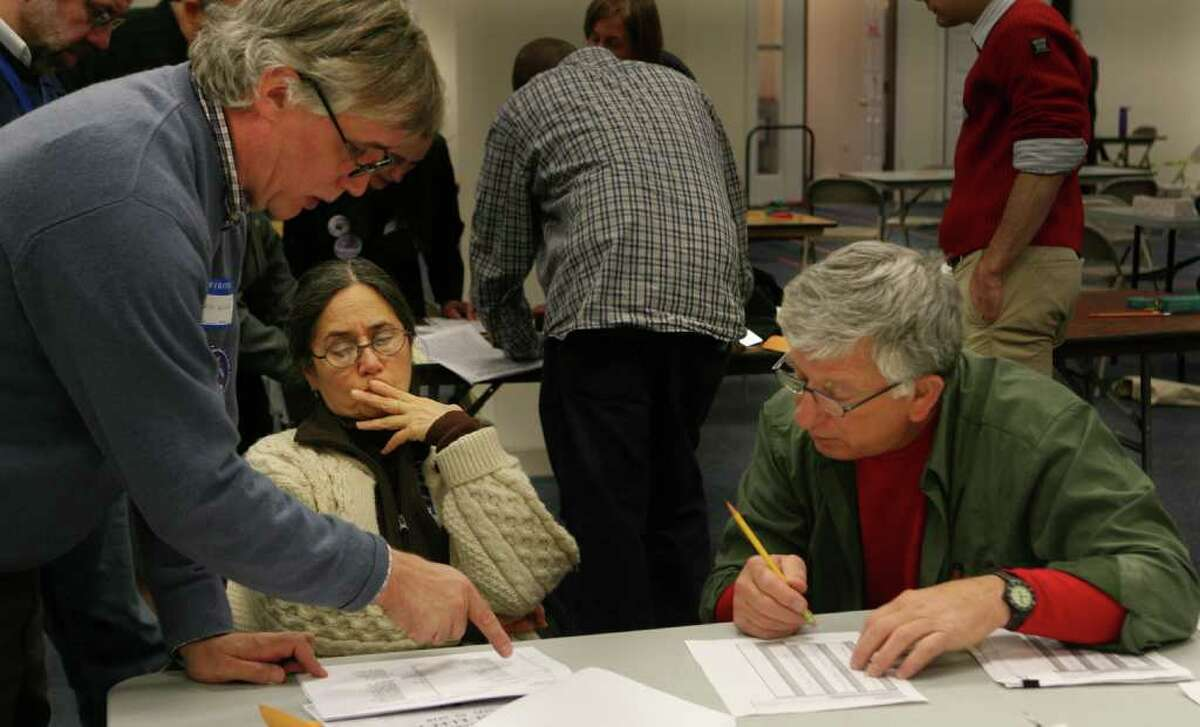 Cyrus Miller, left, answers a question by Pua Ford and Richard Cenami during ballot recounting at the Bridgeport City Hall Annex on Monday, December 6, 2010.