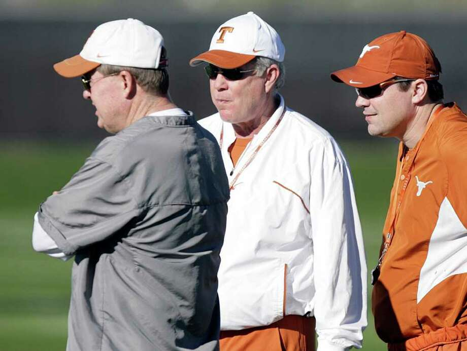Texas coach Mack Brown, center, talks with offensive coordinator Greg Davis, left, and defensive coordinator Will Muschamp, right, during football practice Wednesday, Dec. 31, 2008, in Scottsdale, Ariz. before the Fiesta Bowl NCAA college football game on Monday, Jan. 5, 2009. Davis  resigned Monday. (AP Photo/Paul Connors) Photo: Paul Connors, STR / AP2008