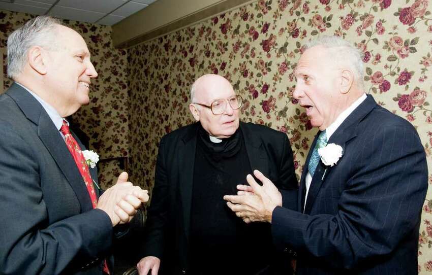 Honorees Richard Rosum, left, and his brother Paul Rosum, right, chat with their cousin Father Robert Hyl as the Stamford Old Timers holds its 68th annual dinner at the Italian Center in Stamford, Conn., Monday, December 6, 2010. Proceeds help fund scholarships for local Scholar-Athletes and sponsorship to area sports teams.