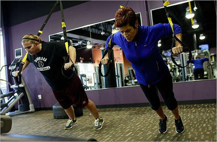 Patricia Jentsch (right) owner of WellFIT Personal Training Group, works with Lindsay Barnes using TRX Suspension Trainers at Anytime Fitness in San Antonio. / SA