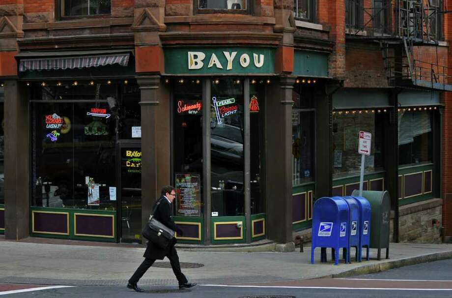 A pedestrian walks past the Bayou Cafe on North Pearl Street in Albany, N.Y.,  on Mon., Dec. 6, 2010. The bar was the scene of a brawl four years ago in which someone who was hurt by a state trooper claims that the bar and the trooper conspired to destroy video evidence of the incident. (Philip Kamrass / Times Union) Photo: Philip Kamrass