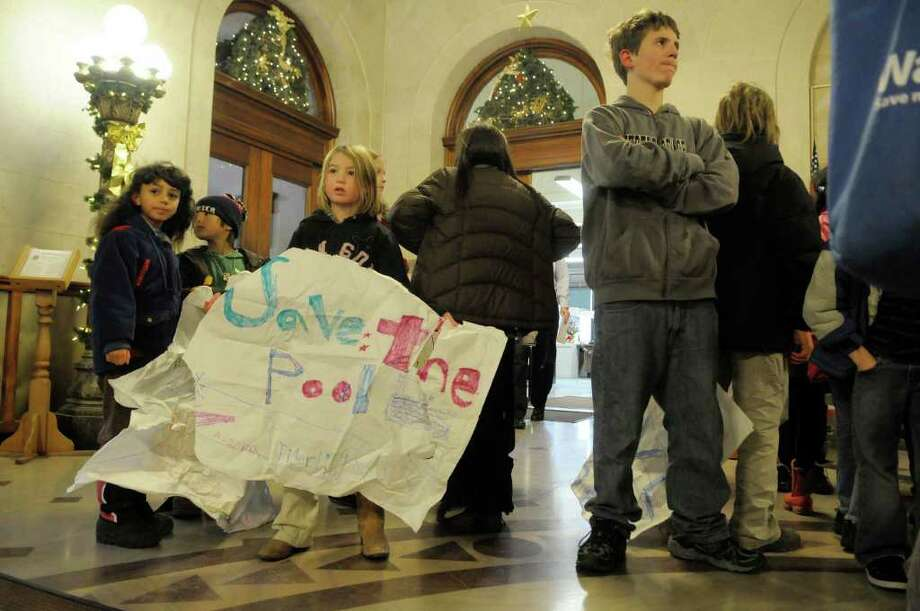 Tigerlily Vanderlaan (cq), center, 7 years old, holds a sign as her fellow students wait with her to talk to Mayor Jerry Jennings  at Albany City Hall in Albany on Monday, Dec. 6, 2010.   Teachers and students from the Albany Free School went to Albany City Hall to talk to the Mayor about his intention to shut down Public Bath #2, which students use on a weekly basis.  Bhawin Suchak, a teacher at the school, said that when the children learned about a month ago that the bath house would be closing, they began to ask questions and Suchak said the school saw it as an opportunity for a lesson in civics.  The students wanted to do something to let the city know how they fell about the bath house and so the trip to City Hall was planned.  Suchak said that roughly 20 kids a week go to the bath house as part of a school program on swimming.   (Paul Buckowski / Times Union) Photo: Paul Buckowski / 00011314A