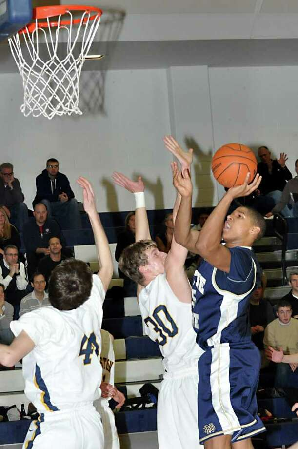 Notre Dame's Arkel Miles goes up for a shot as Weston's Dennis Levene defends during the first period of Friday's boys basketball game at Weston High School. Photo: Amy Mortensen, ST / Connecticut Post