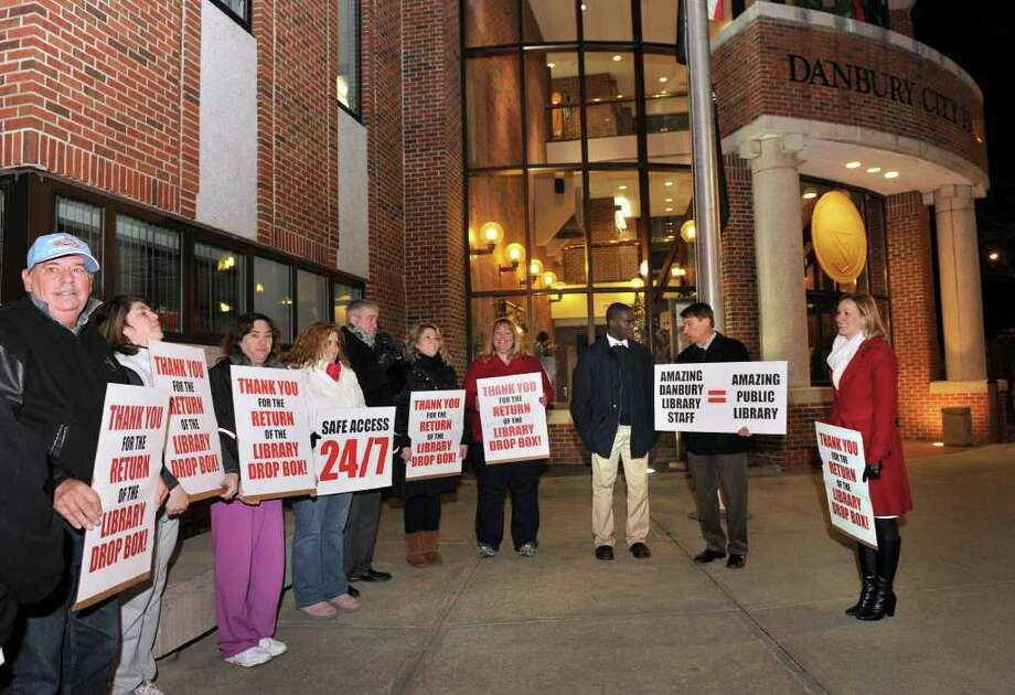 A group of people, most holding signs, held a thank-you rally in front of City Hall Tuesday to thank the mayor and Common Council for the new library drive-up dropbox that should be installed by Wednesday. Photo taken Tuesday, Dec. 7, 2010. Photo: Carol Kaliff / The News-Times