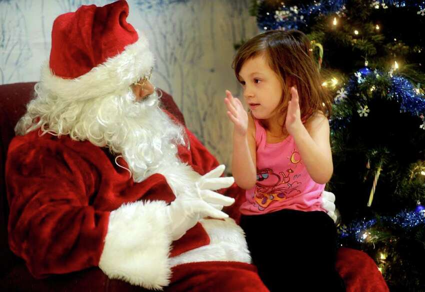 Madison Donnelly, 5, talks to Santa, played by David Torres, at the Ludlowe Center for Health & Rehabilitation in Fairfield. The