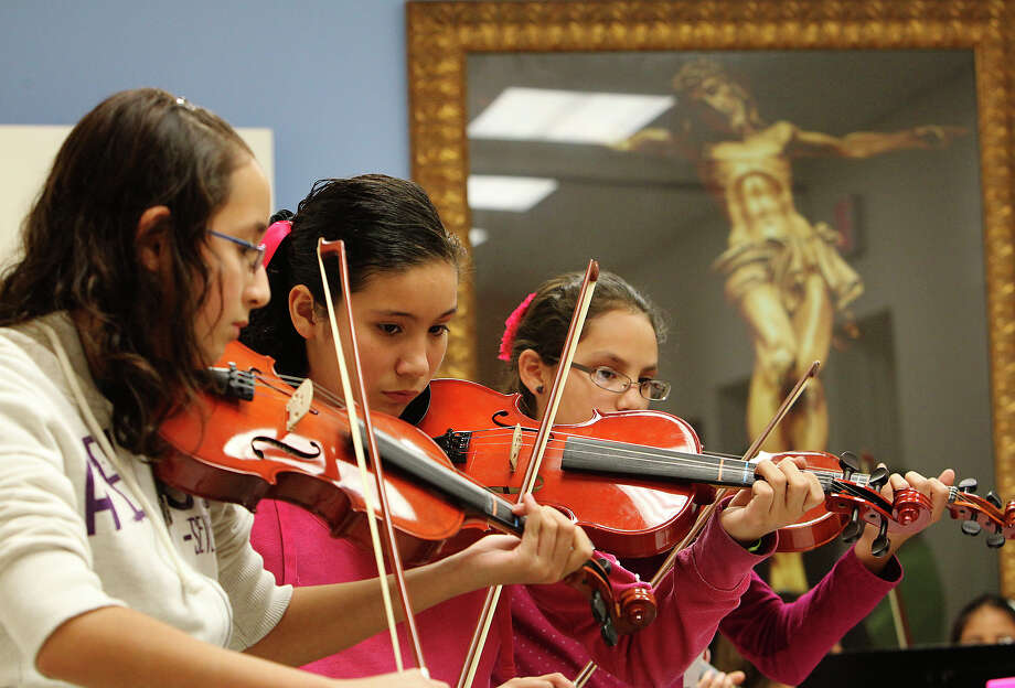 Violinists Sophia Lozano (from left), Samantha Rivas and Nova Morin rehearse at St. Leonard's Catholic Church with Musicales de Tejas. Alejandro Ramirez started the organization to help kids with little musical experience learn mariachi music. Photo: KIN MAN HUI/hmhui@express-news.net