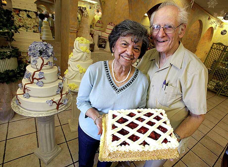 Hans Nadler, right, and his wife Minerva hold their signature cake, Strawberry Shortcake, which they have been making for more than 40 years. Photo: Bob Owen/Express-News