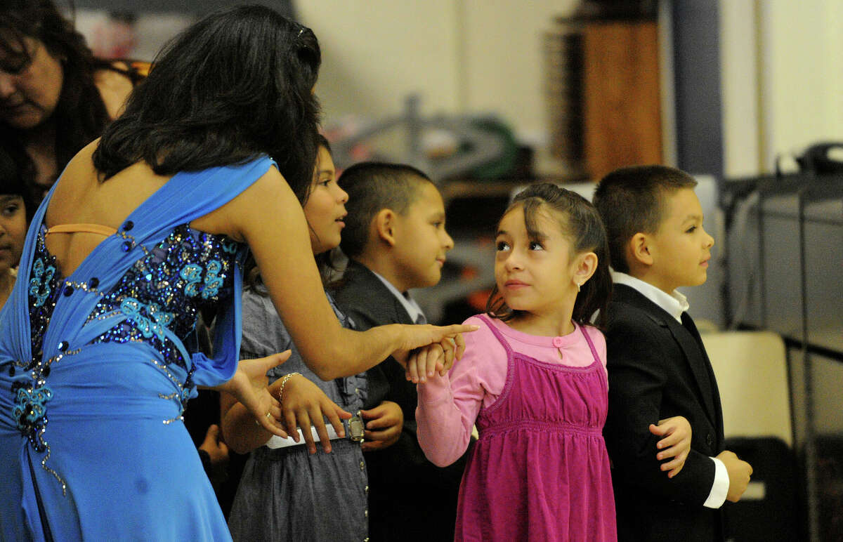 Adriana Araujo offers advice to young dancers Maggie Mae Nevarez and Daniel Vasquez during a ballroom dance contest put on Tuesday, Dec. 7, 2010, at LBJ Elementary School in the Edgewood Independent School District by