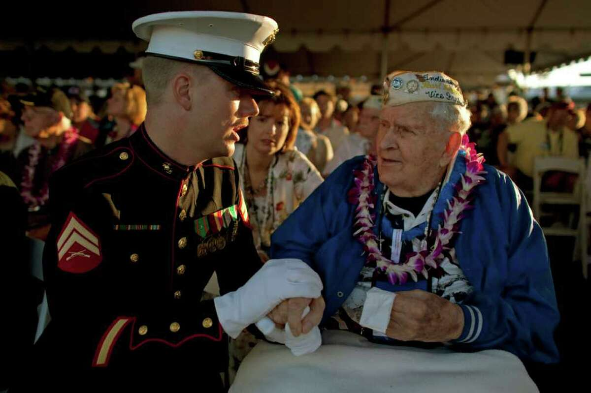 PEARL HARBOR, HI - DECEMBER 7: U.S. Marine Dwight Hanson talks to Pearl Harbor survivor John Latko during a memorial service for 69th anniversary of the attack on the U.S. naval base at Pearl Harbor on the island of Oahu on December 7, 2010 in Pearl Harbor, Hawaii. On the morning of December 7, 1941 a surprise military attack was conducted by aircraft of the Imperial Japanese Navy against the U.S. Pacific Fleet being moored in Pearl Harbor becoming a major catalyst for the United States entering World War II. In the devastating attack over 2,400 people were killed and thousands wounded, and dozens of Navy vessels with were either sunk or destroyed. (Photo by Kent Nishimura/Getty Images)