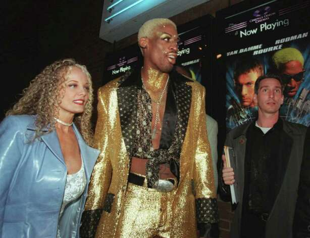 "Chicago Bulls' Dennis Rodman, who wearing his hair in various designs, accompanied by Stacy Yarbough, left, arrives for the world premier of his first movie ""Double Team"" at Chicago's McClurg Court Cinemas Monday, March 31, 1997.  The action-espionage thriller stars Jean-Claude Van Damme, Dennis Rodman and Mickey Rourke. (AP Photo/Mike Fisher) Photo: MIKE FISHER, STR / Beaumont"