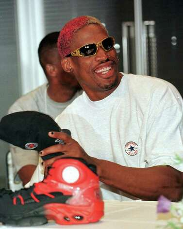 Chicago Bulls' rebounder Dennis Rodman reacts to reporters' questions through an interpreter while preparing to wear his hat during a news conference at the Fuji TV headquarters in Tokyo Friday, July 25, 1997. Rodman arrived today at the invitation of the Japan's TV company to appear on a variety program. (AP Photo/Naokazu Oinuma) Photo: NAOKAZU OINUMA, STF / Beaumont