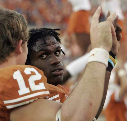 "Texas running back Jamaal Charles, with his trademark dreadlocks,  looks toward quarterback Colt McCoy (12) during the playing of ""The Eyes of Texas,"" after their 28-25 college football victory over Nebraska Saturday, Oct. 27, 2007, in Austin, Texas. Charles ran for fourth-quarter touchdowns of 25, 86 and 40 yards to carry No. 17 Texas to the victory. Charles' 216 yards in the fourth quarter were six shy of the NCAA record for a single quarter.  (AP Photo/Harry Cabluck) Photo: Harry Cabluck, STF / Beaumont"