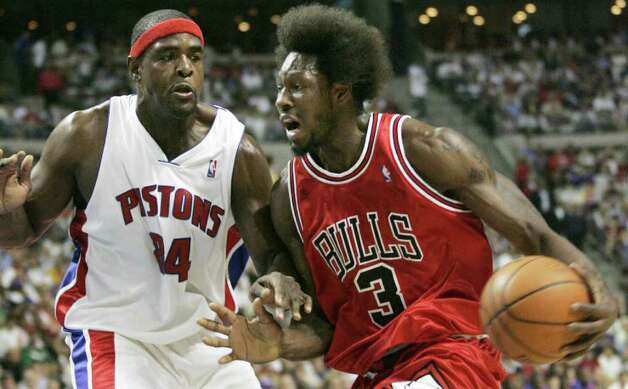 Chicago Bulls center Ben Wallace, wearing his trademark Afro, drives against Detroit Pistons center Chris Webber, during the first half of Game 5 of an NBA second-round playoff basketball series, Tuesday, May 15, 2007, in Auburn Hills, Mich. (AP Photo/Duane Burleson) Photo: Duane Burleson, STR / Beaumont