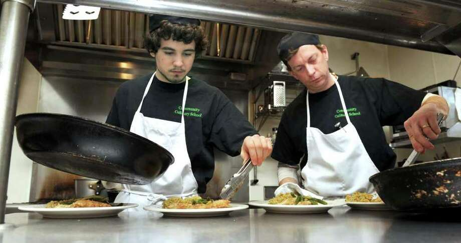 David Bouchard, of Brookfield, left, and Bill Hart, of New Milford, prepare a chicken piccatta lunch for guests Monday at the Community Culinary School in New Milford. Photo taken Monday, Dec. 6, 2010. Photo: Carol Kaliff / The News-Times