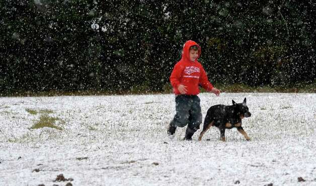 Michael Dahl Jr. and his dog, Rowdy run through the snow near Highway 69 in Kountze, Thursday. Tammy McKinley/ The Enterprise Photo: TAMMY MCKINLEY / Beaumont
